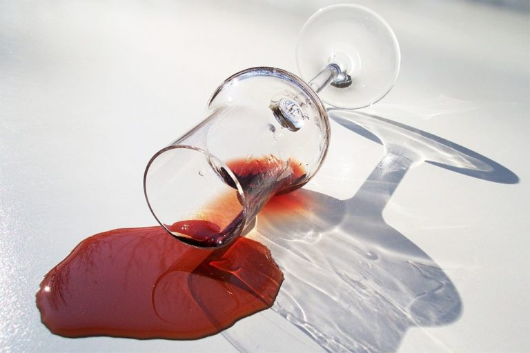 a glass of red wine spilled on a granite countertop
